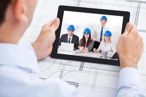arquiteto de videoconferência com a equipe através de tablet digital foto
