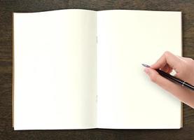 mão escrevendo no livro aberto na mesa foto
