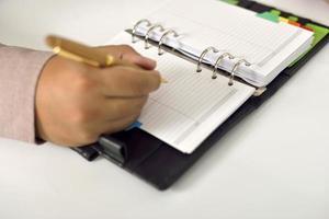 homem de negócios, escrevendo na agenda