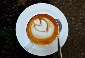café quente com padrão de coração em copo branco foto