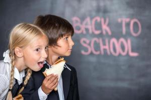imagem engraçada de menino e menina da escola com sanduíches