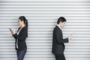 dois colegas de trabalho chineses usando dispositivos de tecnologia foto