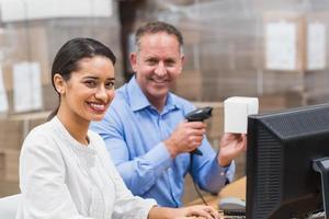 gerente de caixa de digitalização enquanto seu colega digitando no laptop foto