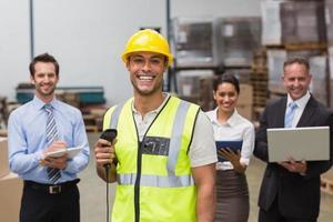 trabalhador de pé com scanner na frente de seus colegas foto