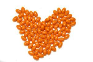 pílulas laranja em forma de coração no fundo branco