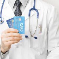 médico com cartões de crédito na mão foto