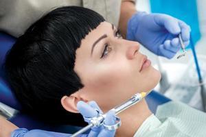 seringa com anestésico perto do dentista do cliente nas bochechas. dentista foto
