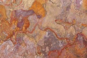 padrão de uma laje de pedra em ferrugem, laranja, bege, roxo foto
