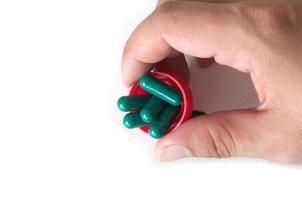 cápsula médica verde em uma mão, isolada foto