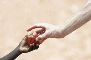 criança africana negra, recebendo nutrição de maçã do médico branco foto
