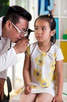 menina asiática durante o exame de ouvido foto