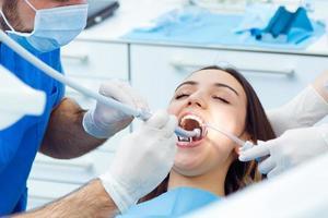 jovem bonita no dentista. exame de boca foto