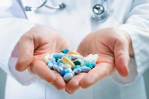 duas mãos segurando uma pilha de comprimidos foto