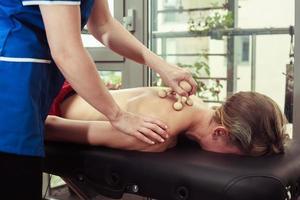 mulher sendo massageada em uma mesa foto