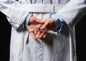 closeup na mulher médico, escondendo a seringa nas costas