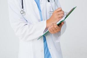 médico escrevendo na área de transferência foto