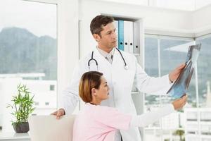 médicos examinando raios-x no consultório médico foto