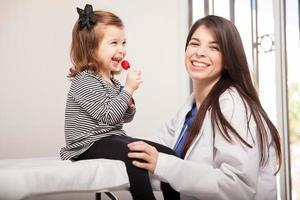 garota feliz com seu pediatra foto