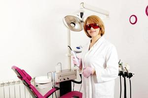 dentista feminina com equipamento no consultório odontológico foto