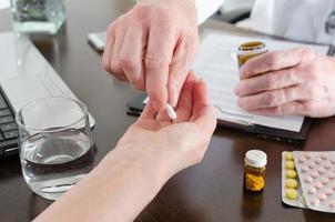 médico dando um comprimido para seu paciente foto