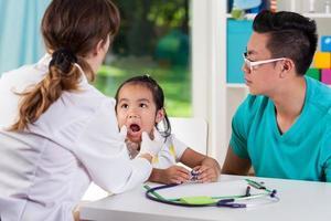 menina asiática com pai no pediatra foto