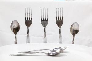 colheres e garfos em um fundo branco foto
