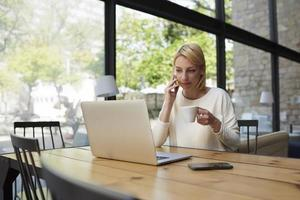 hipster feminino tendo conversa de smartphone trabalhando na mesa de madeira foto