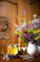 ainda vida de ervas medicinais, mel, chá de ervas e medicamentos foto