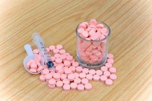 comprimidos cor de rosa e seringa na mesa para o conceito de cuidados de saúde foto