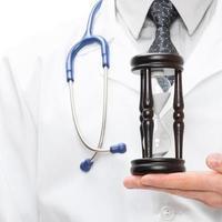 médico holdling na mão uma ampulheta - conceito de saúde foto
