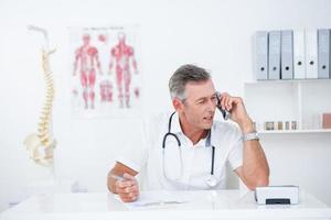 médico escrevendo na área de transferência e telefonando
