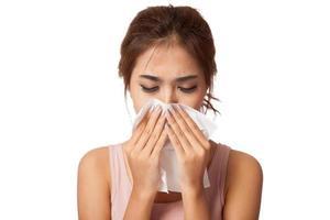 menina bonita asiática pegou um resfriado. espirros em tecido. foto