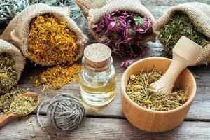 ervas medicinais em sacos de juta, argamassa com camomila e óleo foto