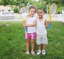 duas crianças sorrindo felizes segurando raquetes de tênis foto