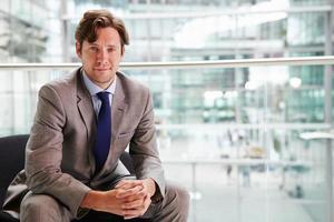 empresário corporativo sentado no interior moderno, retrato