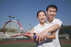 jovem jogando tênis com seu treinador foto
