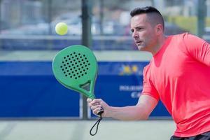 homem jogando tênis de raquete ao ar livre foto