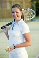 jovem garota feliz com uma raquete de tênis foto