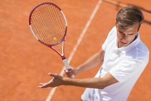 jovem jogando tênis foto