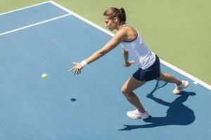 jovem mulher jogando tênis foto