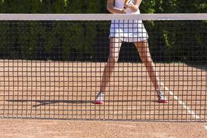 pernas finas de atleta feminina de tênis atrás da barreira de rede de pesca foto