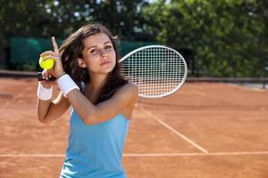 jovem garota segurando uma bola de tênis na quadra foto