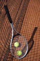 bolas de tênis e foguetes no campo de tribunal foto