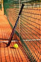 bola e raquete de tênis estão perto da rede vertical foto