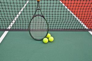 quadra de tênis com bola e raquete foto