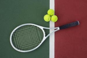 raquete de tênis e bolas na quadra de tênis foto