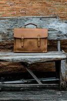 bolsa de laptop de couro marrom corporativa na cadeira de madeira velha foto