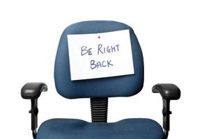 estar de volta sinal fixado na cadeira azul do escritório foto