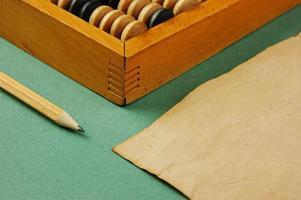 ábaco velho e caderno sobre o fundo verde foto