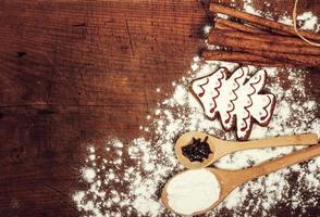 Biscoitos de Natal, especiarias e farinha na tábua de madeira foto
